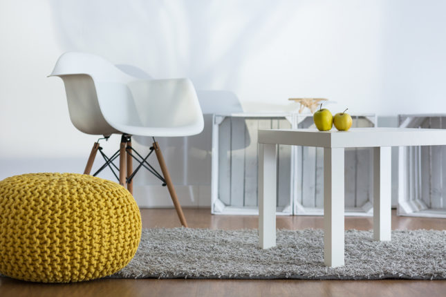 Yellow pouf, white armchair and coffee table in modern designed loft